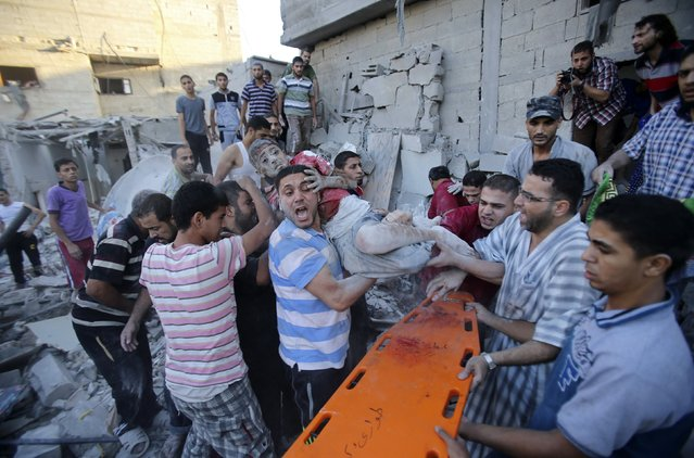 Palestinians carry a wounded a boy who was evacuated from under the rubble of a house, which witnesses said was destroyed in an Israeli air strike, in Rafah in the southern Gaza Strip  August 3, 2014. (Photo by Ibraheem Abu Mustafa/Reuters)