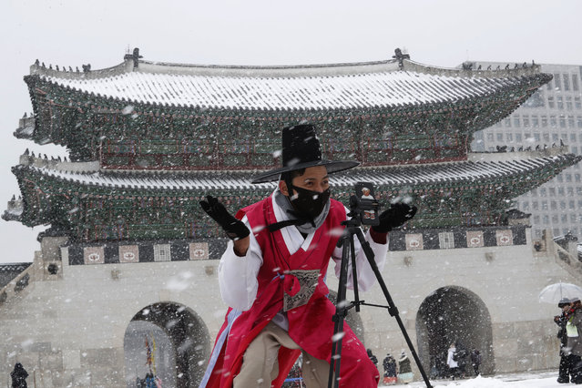 """A man dressed in South Korean traditional """"Hanbok"""" attire wears a face mask in the snow as he gestures to take photos at the Gyeongbok Palace, the main royal palace during the Joseon Dynasty in Seoul, South Korea, Monday, February 17, 2020. Chinese authorities on Monday reported a slight upturn in new virus cases and hundred more deaths for a total of thousands since the outbreak began two months ago. (Photo by Ahn Young-joon/AP Photo)"""