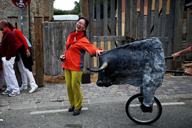 A woman is surprised by a toy bull during the Encierro Txiki (Little Bull Run) during the San Fermin festival in Pamplona, Spain July 13, 2016. (Photo by Susana Vera/Reuters)
