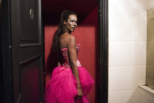 In this August 25, 2017 photo, a reveler leaves the women's bathroom during Nostalgia Night parties in Montevideo, Uruguay. Although the original Nostalgia Night party took place in one venue when it started in 1978, many others took notice an now the party takes place all over the country. (Photo by Matilde Campodonico/AP Photo)