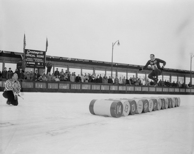 Terry Browne, 33-year-old Detroit, Mich., fireman, is at the halfway mark as he sails over 14 barrels, a distance of 27 feet, nine inches, to win the World Barrel Jumping Championship at Grossinger, N.Y., January 11, 1953. (Photo by AP Photo)