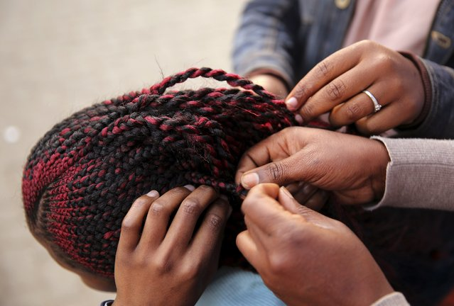 Hairdressers braid the hair of a client in downtown Johannesburg. While South Africans change their hairstyle often, West Africans do so even more, said Bertrand de Laleu, managing director of L'OrealSouth Africa. (Photo by Siphiwe Sibeko/Reuters)