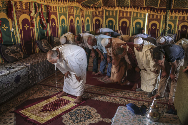 In this Thursday, August 17, 2017 photo, people pray in a tent before the start of Tabourida, a traditional horse riding show also known as Fantasia, in Mansouria, near Casablanca, Morocco. (Photo by Mosa'ab Elshamy/AP Photo)