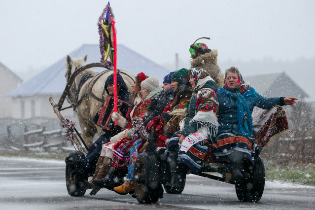People in folk costumes ride in a horse drawn carriage to sing Christmas carols known as kolyadki in the village of Dubrovka in Brest Region, Belarus on January 7, 2020. Kolyadki is a Slavic Christmas tradition. Groups of people dressed in folk costumes come to houses to sing Christmas carols and receive treats from the hosts. (Photo by Natalia Fedosenko/TASS)