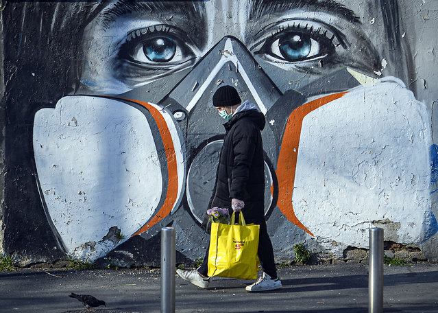 A man walks with his groceries beside a mural painting that portrays a person wearing a gas mask, Milan, Italy, 16 March 2020. Italy is under lockdown in an attempt to prevent the spread of the pandemic Coronavirus. Several European countries have closed borders, schools as well as public facilities, and have cancelled most major sports and entertainment events in order to prevent the spread of the SARS-CoV-2 Coronavirus causing the Covid-19 disease. (Photo by Andrea Fasani/EPA/EFE)