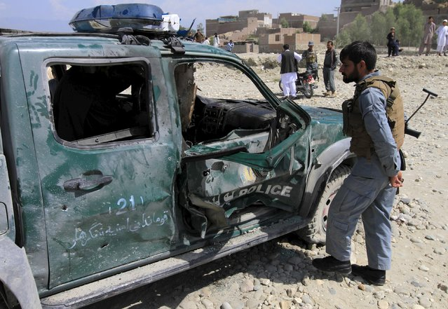 An Afghan policeman inspects the wreckage of a police car which had a magnetic bomb attached, at the site of a bomb explosion in Jalalabad, Afghanistan August 31, 2015. At least one policeman was killed and three others were wounded in the blast, the provincial police spokesman Hazrat Hussin Mashriqiwal said. (Photo by Reuters/Parwiz)