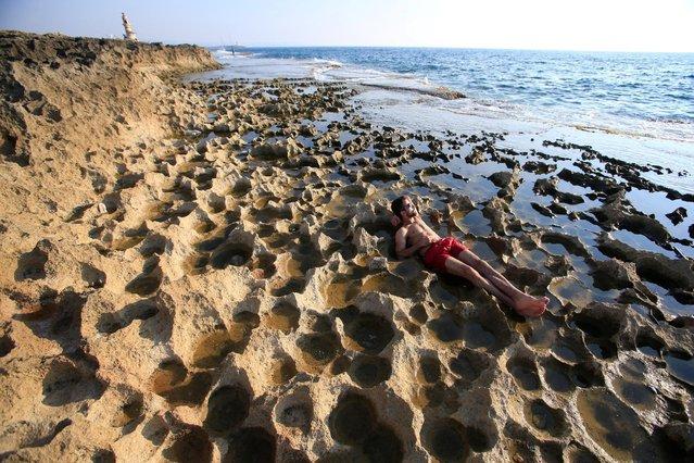 A man enjoys the beach at a tiny island in Sidon, southern Lebanon, July 17, 2016. (Photo by Ali Hashisho/Reuters)