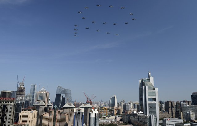 """A formation of military helicopters, forming the figure """"70"""", flies past the central business area (CBD) of Beijing, China during the military parade marking the 70th anniversary of the end of World War Two, September 3, 2015. (Photo by Reuters/Stringer)"""