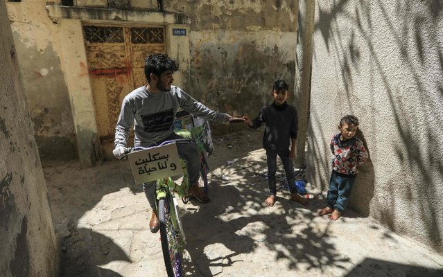 A Palestinian volunteer for the Women's Program Center rides a bicycle as he distributes crafts and reading material to children in confinement due to the novel coronavirus pandemic, in the central Deir al-Balah refugee camp in the Gaza Strip, on April 12, 2020. (Photo by Mahmud Hams/AFP Photo)