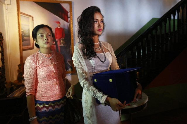 Myanmar's former beauty queen May Myat Noe (R), holding the box containing the 2014 Miss Asia Pacific World crown, stands next to her mother before giving a news conference at a restaurant in Yangon September 2, 2014. (Photo by Soe Zeya Tun/Reuters)