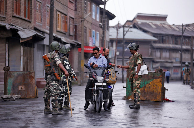 Indian policemen check identity papers of Kashmiri men on their motorcycles during a curfew in Batamaloo area of Srinagar August 2, 2016. (Photo by Danish Ismail/Reuters)