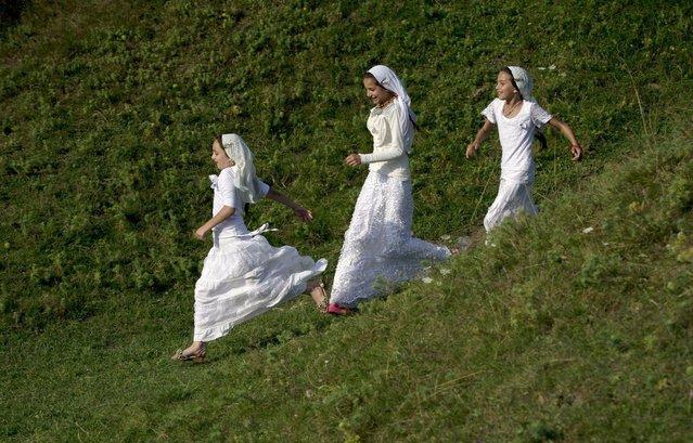 Romanian Roma girls run as the Roma community celebrates the Birth of the Virgin Mary in Costesti, Romania, Monday, September 8, 2014. (Photo by Vadim Ghirda/AP Photo)