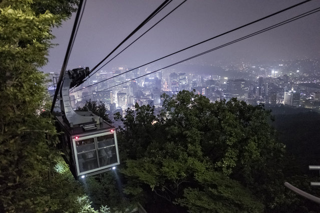 A cable car with passengers descends to ground from the top of Namsan mountain on July 30, 2015 in Seoul, South Korea. North side of the City of Seoul is seen down the mountain. (Photo by Shin Woong-jae/The Washington Post)