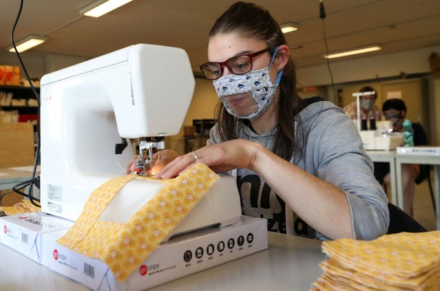 """A worker of the bookbinding factory """"Brochage-Renaitre"""", which employs mainly people with disabilities, sews a special protective mask designed with a partially transparent area that allows deaf people to read lips, amid the coronavirus disease (COVID-19) outbreak, in Brussels, Belgium, May 19, 2020. (Photo by Yves Herman/Reuters)"""