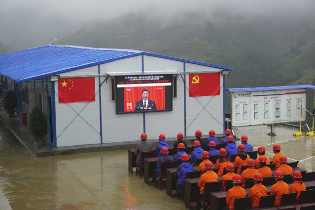 """Road construction workers watch a screen showing a speech by Chinese President Xi Jinping during the opening ceremony of the 19th Party Congress in Congjiang county in southwestern China's Guizhou province Wednesday, October 18, 2017. Xi on Wednesday urged a reinvigorated Communist Party to take on a more forceful role in society and economic development to better address """"grim"""" challenges facing the country as he opened a twice-a-decade national congress. (Photo by Chinatopix via AP Photo)"""