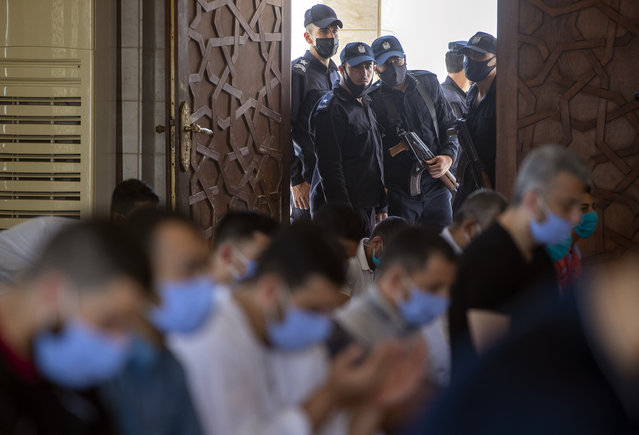 Palestinian Hamas police stand guard at the entrance of a mosque as worshipers attend the last Friday noon Prayer of the holy month of Ramadan, in Gaza City, Friday, May. 22, 2020. After nearly two months of closure due to the coronavirus, Gaza's Hamas rulers decided to partially reopen mosques for the Friday noon prayer. (Photo by Khalil Hamra/AP Photo)
