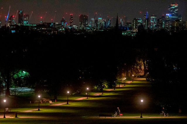 Cyclists take their daily exercise allowance through the park at night in Primrose Hill in London on April 18, 2020, during the novel coronavirus COVID-19 pandemic. The number of people in Britain who have died in hospital from coronavirus has risen by 888 to 15,464, according to daily health ministry figures on Saturday. (Photo by Justin Tallis/AFP Photo)