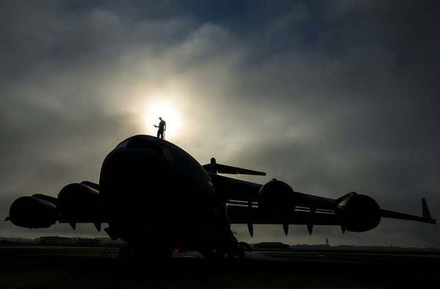 Tech. Sgt. Andrew Gravett walks along the top of a C-17 Globemaster III as he does a routine maintenance check at Joint Base Charleston, S.C. The first C-17 to enter the Air Force's inventory arrived at Charleston Air Force Base in June 1993. (Photo by USAF)