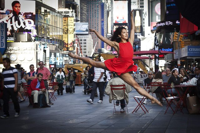 """A dancer poses for a photograph as part of the """"Dance as Art"""" photo project in Times Square in New York September 22, 2014. The project is a celebration of dancers and their place in the New York experience. (Photo by Carlo Allegri/Reuters)"""