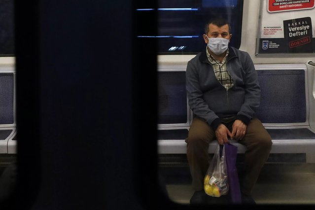 A man wearing facemasks for protective measures sits in the subway train as the spread of the COVID-19, the novel coronavirus continues in Ankara, on April 16, 2020. (Photo by Adem Altan/AFP Photo)