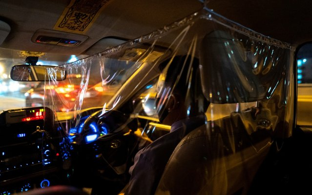 A taxi driver is pictured through a plastic barrier and social distancing he installed in order to prevent the spread of the coronavirus disease (COVID-19) in Bangkok, Thailand, May 12, 2020. (Photo by Athit Perawongmetha/Reuters)