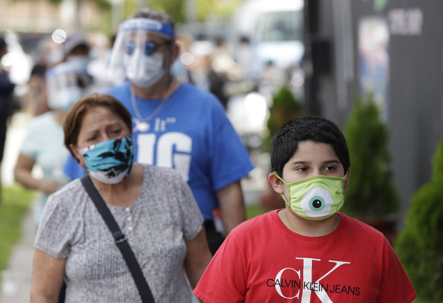 People, social distancing and wearing masks to prevent the spread of the new coronavirus, wait in line at a mask distribution event, Friday, June 26, 2020, in a COVID-19 hotspot of the Little Havana neighborhood of Miami. Florida banned alcohol consumption at its bars Friday as its daily confirmed coronavirus cases neared 9,000, a new record that is almost double the previous mark set just two days ago. (Photo by Wilfredo Lee/AP Photo)