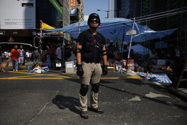 "Andy Yung, 30, a lifeguard, poses on Nathan Road in Mongkok shopping district in Hong Kong October 7, 2014. Yung said, ""I come here to protect the students from being attacked and  I support real universal suffrage"". (Photo by Bobby Yip/Reuters)"