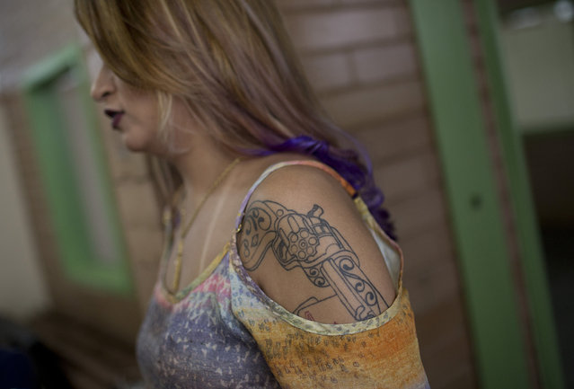 A tattoo of a weapon covers the arm of a female inmate waiting to compete in the annual beauty contest at Talavera Bruce penitentiary in Rio de Janeiro, Brazil, early Thursday, November 23, 2017. (Photo by Silvia Izquierdo/AP Photo)
