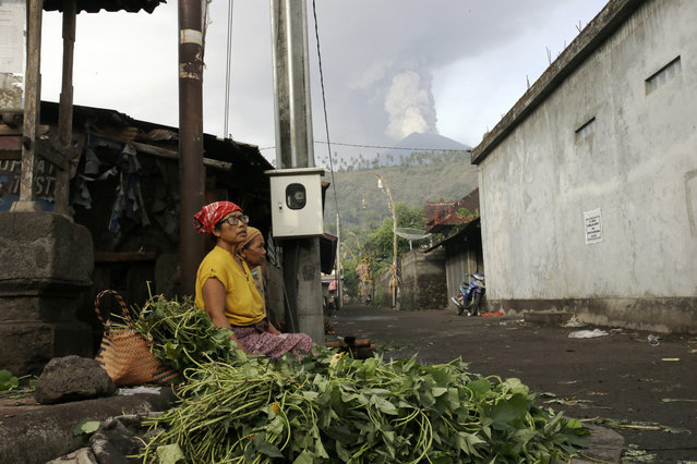 Vegetables sellers wait for customers at a market with a backdrop of the Mount Agung volcano erupting in Karangasem, Indonesia, Monday, November 27, 2017. Indonesia authorities raised the alert for the rumbling volcano to highest level on Monday and closed the international airport on tourist island of Bali stranding thousands of travelers. (Photo by Firdia Lisnawati/AP Photo)