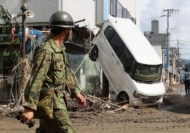 An officer walks psat a damaged car in Hitoyoshi, in Kumamoto Prefecture on July 8, 2020. Japan will deploy more troops to search for survivors of devastating floods and landslides that have killed at least 52 people in the southwest of the country, Prime Minister Shinzo Abe pledged. (Photo by JIJI Press/AFP Photo/Stringer)