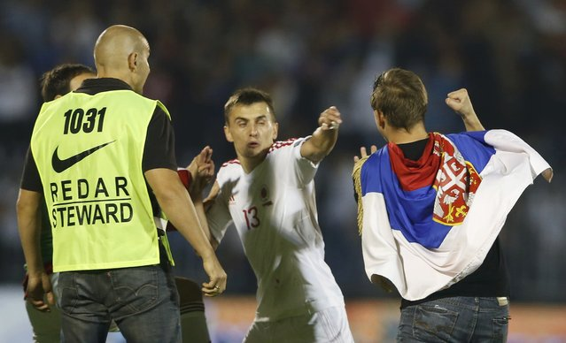 Albania's Burim Kukeli (C) and a teammate (hidden) clash with fan of Serbia during their Euro 2016 Group I qualifying soccer match at the FK Partizan stadium in Belgrade October 14, 2014. (Photo by Marko Djurica/Reuters)