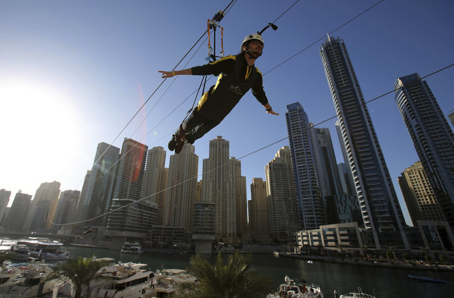 A man rides the world's longest urban zip line, with a speed of up to 80 kilometers per hour on a one kilometer run from 170 meter to ground level, in the Marina district of Dubai, United Arab Emirates, Tuesday, December 5, 2017. (Photo by Kamran Jebreili/AP Photo)