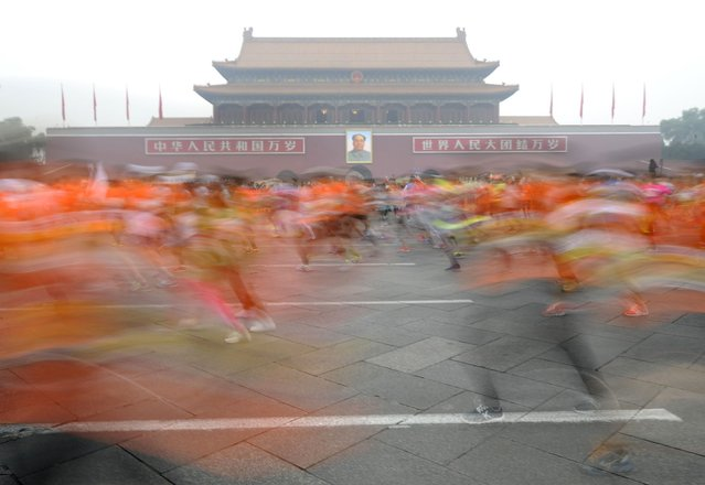 Participants run past the Tiananmen gate with a portrait of China's late leader Mao Zedong during a hazy day at the Beijing International Marathon, Beijing October 19, 2014. (Photo by Reuters/Stringer)