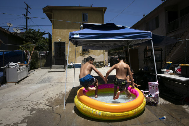 Vincent Velarde, 11, left, and his brother, Emilio, 12, jump into an inflatable pool in Los Angeles, Friday, July 17, 2020. California Gov. Gavin Newsom laid out strict criteria Friday for school reopenings that makes it unlikely the vast majority of districts will have classroom instruction in the fall as the coronavirus pandemic surges. (Photo by Jae C. Hong/AP Photo)