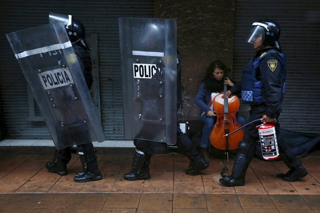 Police carry shields and a fire extinguisher while a woman plays a cello during a march to mark the first anniversary of the disappearance of students from Ayotzinapa College Raul Isidro Burgos, in Mexico City, September 26, 2015. (Photo by Edgard Garrido/Reuters)