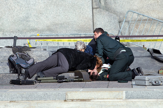 Police, bystanders and soldiers aid a fallen soldier at the War Memorial as police respond to an apparent terrorist attack  on October 22, 2014 in Ottawa, Canada. A gunman is believed to have shot a soldier as he was standing guard at the National War Memorial in Ottawa, Canada, this morning (Wednesday, October 22). (Photo by Wayne Cuddington/Postmedia/Barcroft Media /ABACAPress)