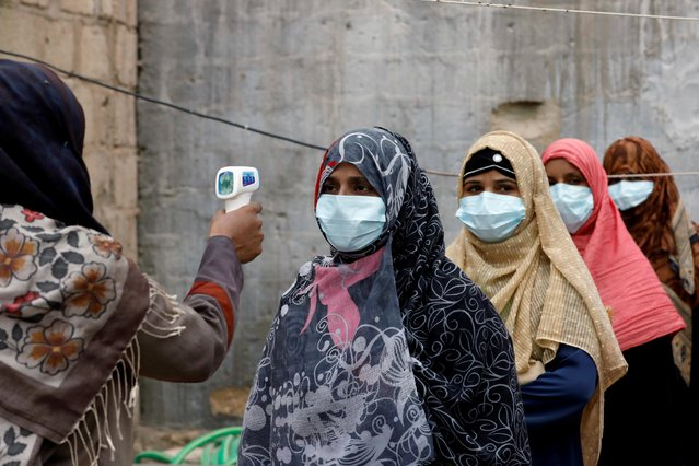 Vaccinators wear protective masks as they get their temperature checked, during an anti-polio campaign, in a low-income neighborhood as the spread of the coronavirus disease (COVID-19) continues, in Karachi, Pakistan on July 20, 2020. (Photo by Akhtar Soomro/Reuters)