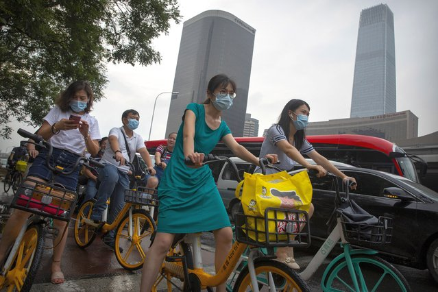 People wearing face masks to protect against the coronavirus wait at an intersection in the central business district in Beijing, Friday, July 31, 2020. China is tightening travel restrictions in the capital of Xinjiang, where more than a hundred new cases were reported Friday. (Photo by Mark Schiefelbein/AP Photo)