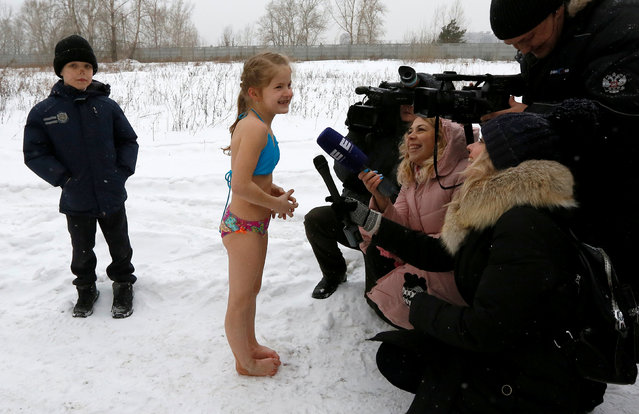 Journalists interview a girl, member of the Cryophile amateurs winter swimmers club, after bathing in the ice waters of the Yenisei River, during the celebrations for the upcoming Christmas and New Year, in Krasnoyarsk, Russia, December 23, 2017. (Photo by Ilya Naymushin/Reuters)