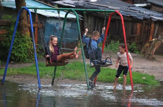 Children play on swings on a flooded playground after rain in the town of Kokhma in Ivanovo Region, Russia on July 22, 2020. (Photo by Vladimir Smirnov/TASS)