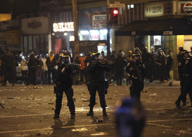 Police take aim at a crowd gathered in the Mission District in San Francisco, California October 29, 2014. (Photo by Robert Galbraith/Reuters)