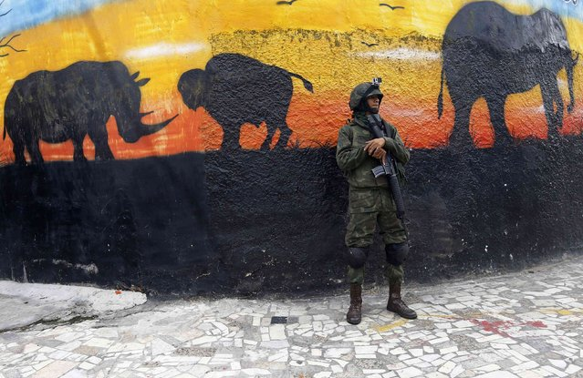 A Brazilian Navy soldier patrols next to a polling station in Mare slums complex in Rio de Janeiro October 26, 2014. Brazilians were voting on Sunday in an election that pits a leftist president with strong support among the poor against a centrist senator who is promising pro-business policies to jumpstart a stagnant economy. (Photo by Ricardo Moraes/Reuters)