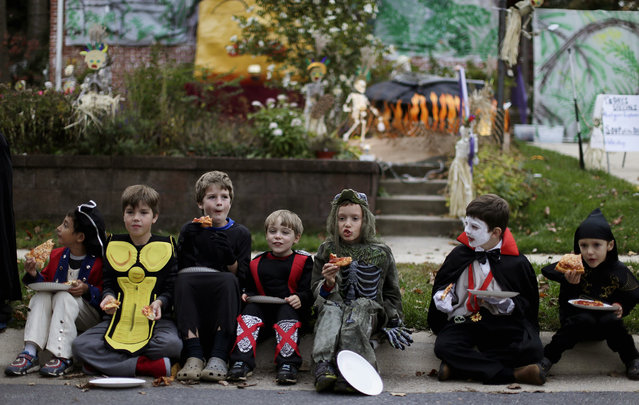 Children dressed in costumes eat pizza at the Flint family's annual Halloween block party in Silver Spring, Maryland October 31, 2014. The Flint's have decorated their house and thrown a theme block party for the last 17 years for neighborhood children and adults before the annual trick or treating. (Photo by Gary Cameron/Reuters)