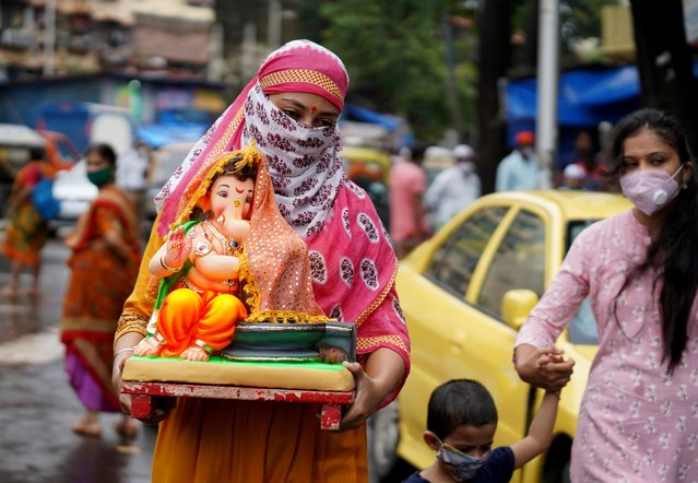 A woman carries an idol of Hindu god Ganesh to her home on the first day of the ten-day-long Ganesh Chaturthi festival, amid the coronavirus disease (COVID-19) outbreak, in Mumbai, India on August 22, 2020. (Photo by Hemanshi Kamani/Reuters)