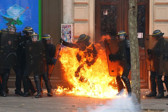 A French riot police officer gesturea as he is surrounded by flames, during a demonstration against the controversial labour reforms of the French government in Paris on September 15, 2016. (Photo by Thomas Samson/AFP Photo)