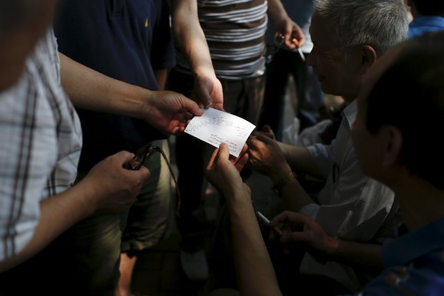 """A piece of paper stock information written on it is shared by investors during a """"street stock salon"""" in central Shanghai, China, June 20, 2015. (Photo by Aly Song/Reuters)"""