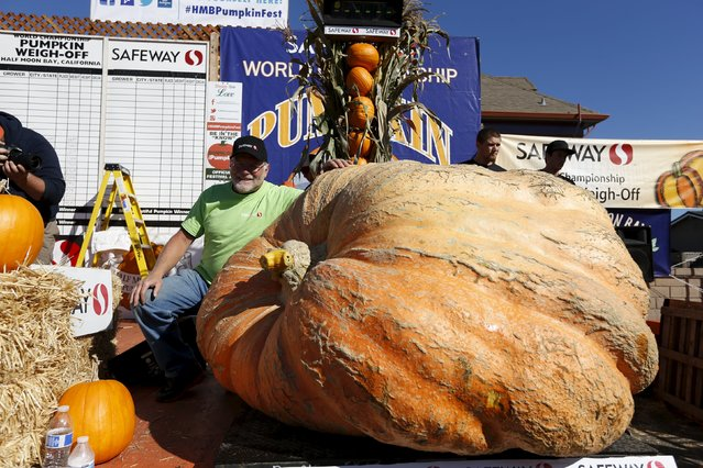 Jack Larue, of Tenino, Washington, poses with his third place 1,685 pound pumpkin during the 42nd annual Safeway World Championship Pumpkin Weigh-off in Half Moon Bay, California October 12, 2015. (Photo by Stephen Lam/Reuters)