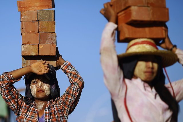 """Construction workers carry bricks on their heads near the country's parliament building in Naypyitaw November 11, 2014. Yangon lost its status as Myanmar's capital in 2005, after the former military junta carved a new seat of government from a parched wilderness some 380 km (236 miles) to the north and called it Naypyitaw (""""Abode of Kings""""). (Photo by Damir Sagolj/Reuters)"""