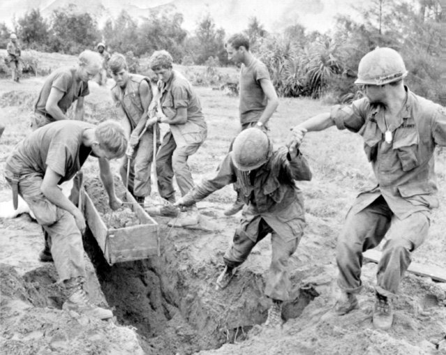 American troops pull a sand covered wooden box, in which enemy weapons were hidden, from a large hole in the Batangan Peninsular, 60 miles south of Danang, South Vietnam, on January 24, 1969. (Photo by AP Photo)