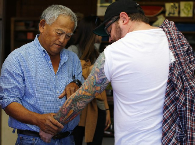 Farmer Tom Chino (L) looks at tattoos of vegetables on the arm of southern cuisine Chef Sean Brock as Brock visits the Chino family farm in Rancho Santa Fe, California November 16, 2014. (Photo by Mike Blake/Reuters)